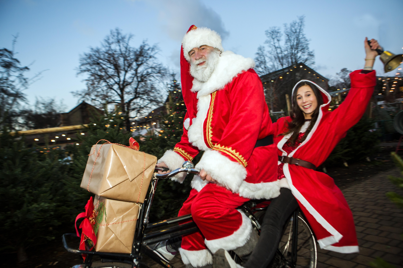 Weihnachtsmarkt in den Späth'schen Baumschulen mit Weihnachtsmann und Weihnachtsfrau auf dem Fahrrad