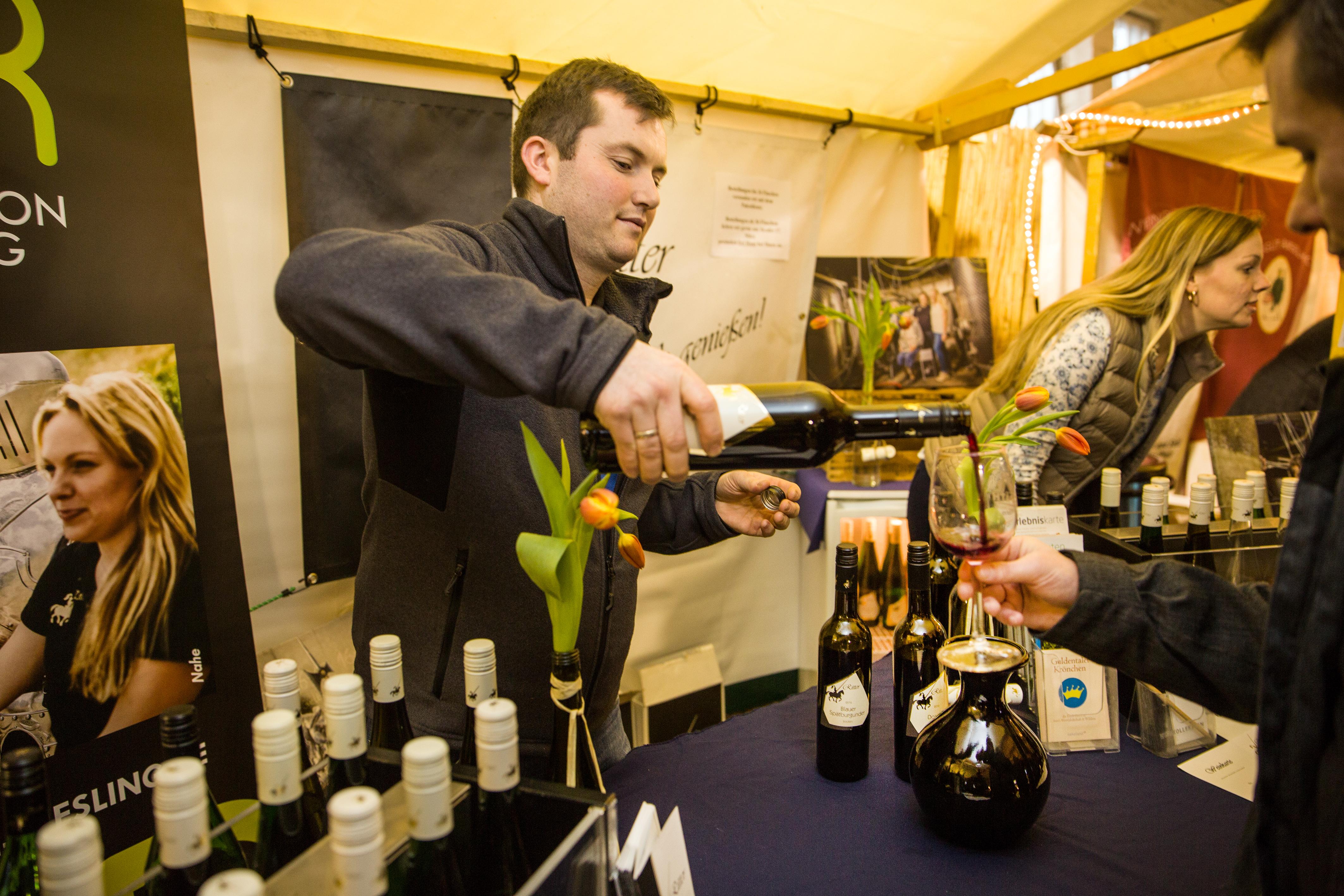 Winzer Ritter von der Nahe schenkt einem Gast Rotwein ein