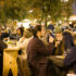 Blick in die historische Packhalle: Gäste trinken Wein an großen Tischen.