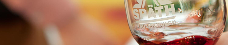Weinglas mit Späth-Logo vor hellem Hintergrund