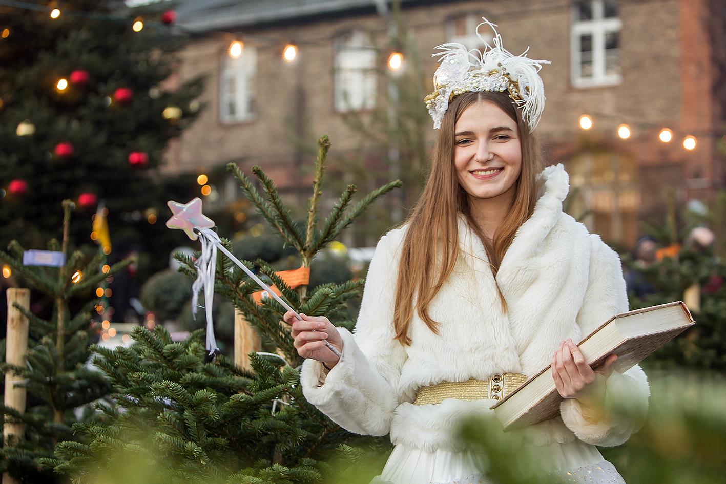 Weihnachtsengel mit Kopfschmuck und Zauberstab vor Weihnachtsbäumen