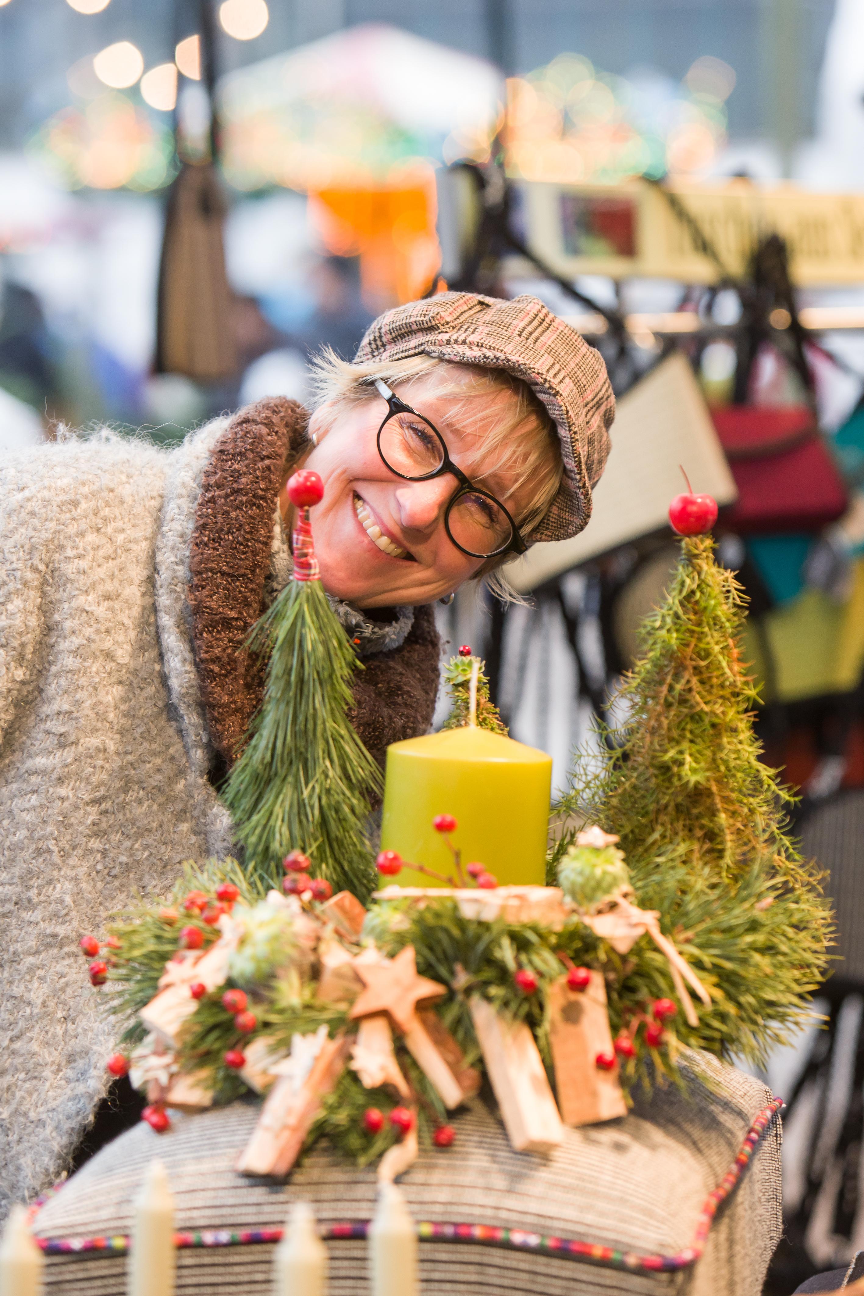 Dame mit strahlendem Lachen beugt sich über ein Adventsgesteck
