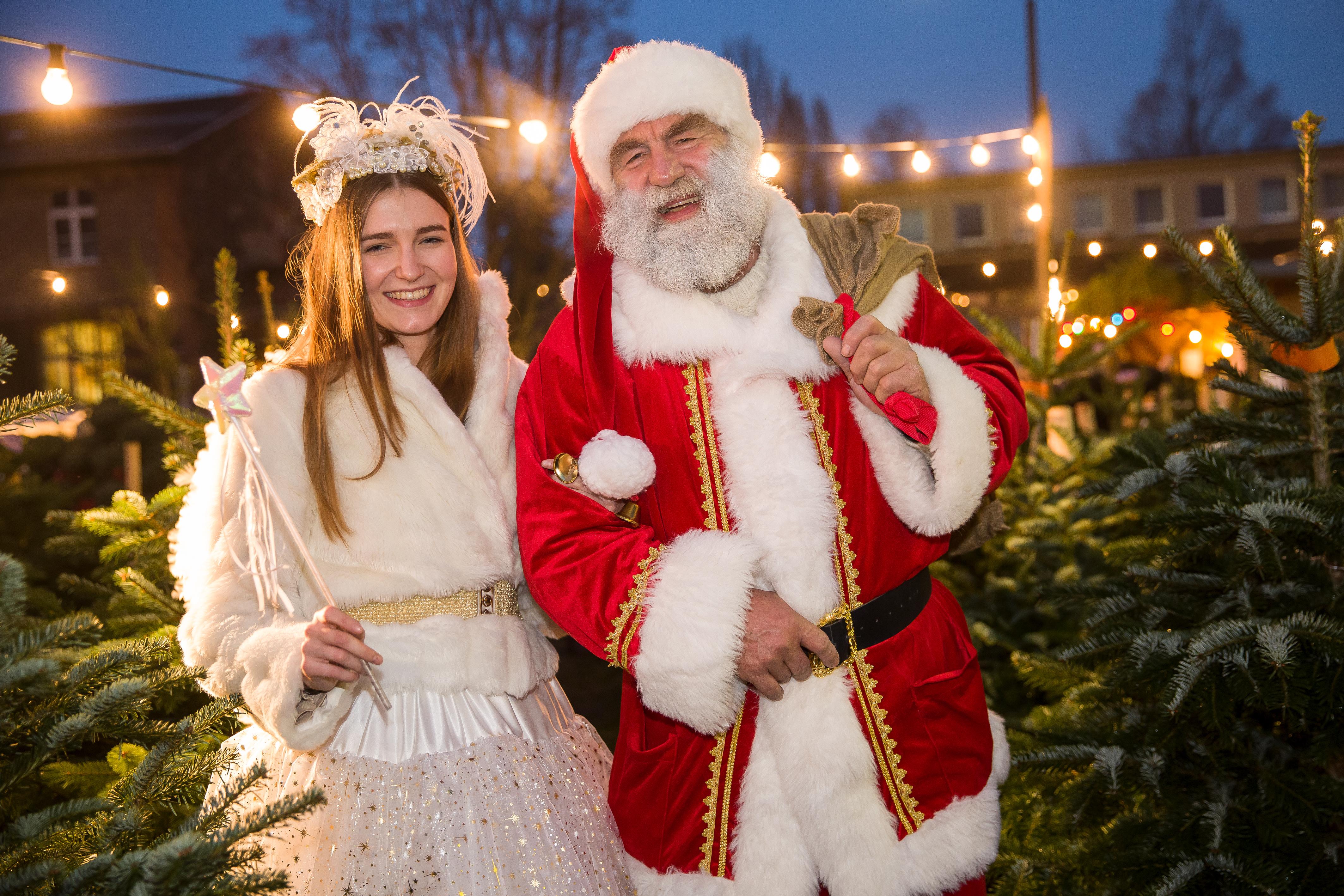 Engel und Weihnachtsmann inmitten eines Tannenwaldes