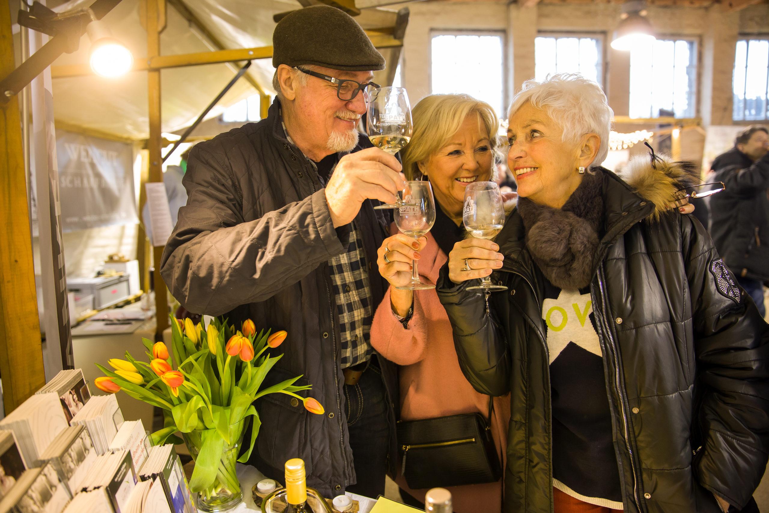Besucher prosten sich beim Weinfest in der historischen Packhalle zu