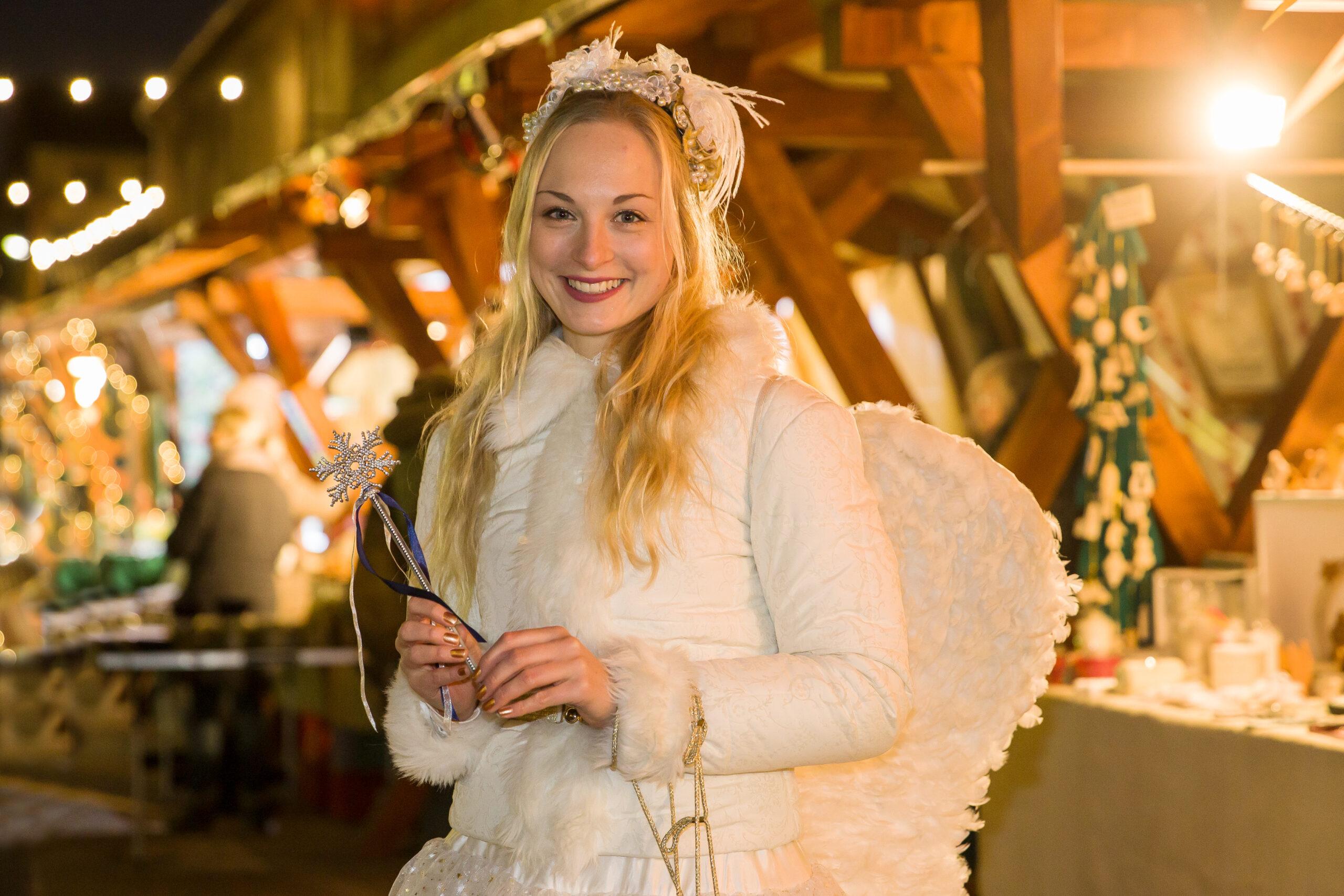 Blonder Engel vor Ständen mit Geschenkideen