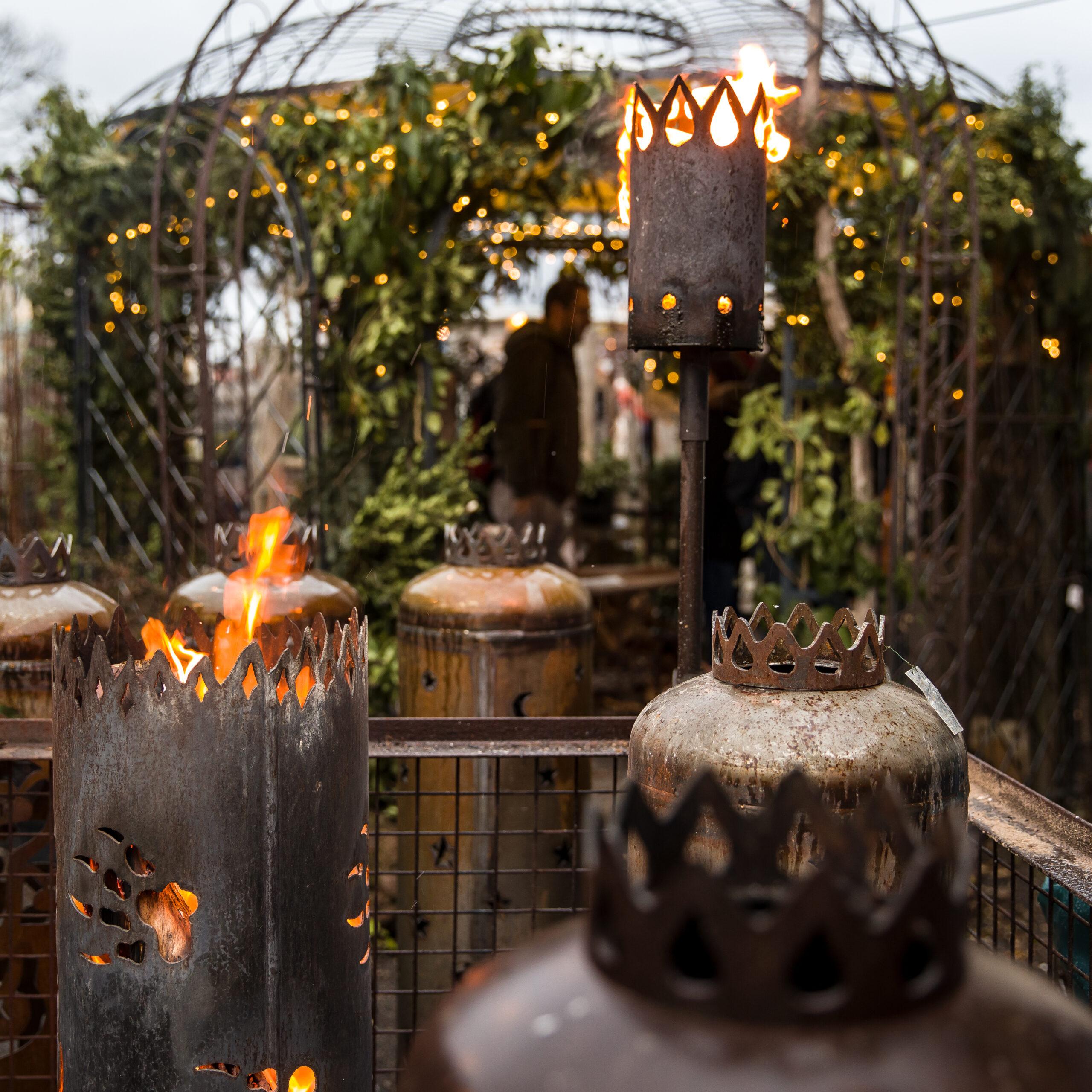 Feuerfackeln aus Metall vor Pavillon mit geschmückten Tannenzweigen
