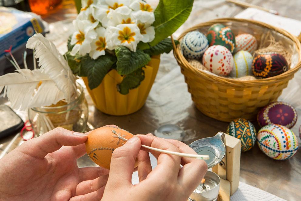 Ein Osterei wird bemalt, daneben ein Korb mit bemalten Eiern