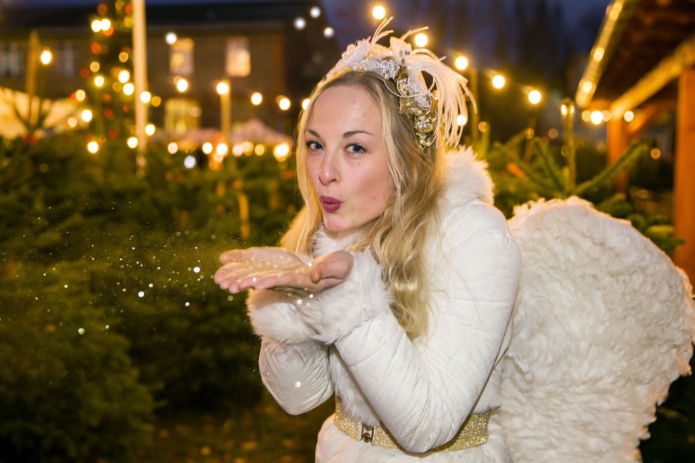 Blonder Engel pustet Goldstaub mitten im Tannenwald